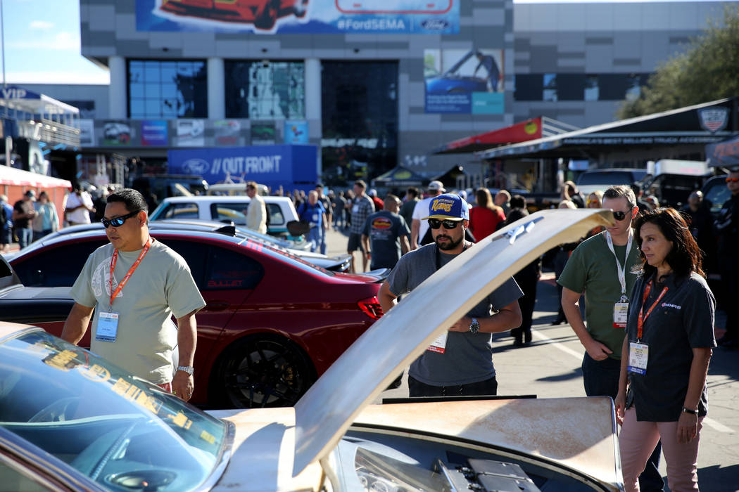 Aaron Sakahara of Sacramento, Calif., left, shows his 1959 Buick Invicta to Michael Anderson of ...