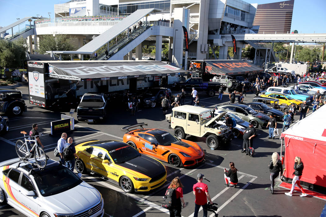 Conventioneers check out cars at the Specialty Equipment Market Show at the Las Vegas Conventio ...