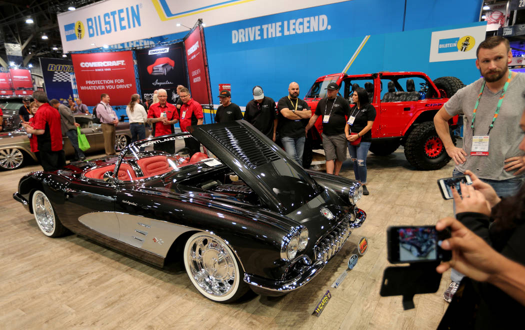 Conventioneers check out a 1958 Corvette at the Covercraft booth at the Specialty Equipment Mar ...