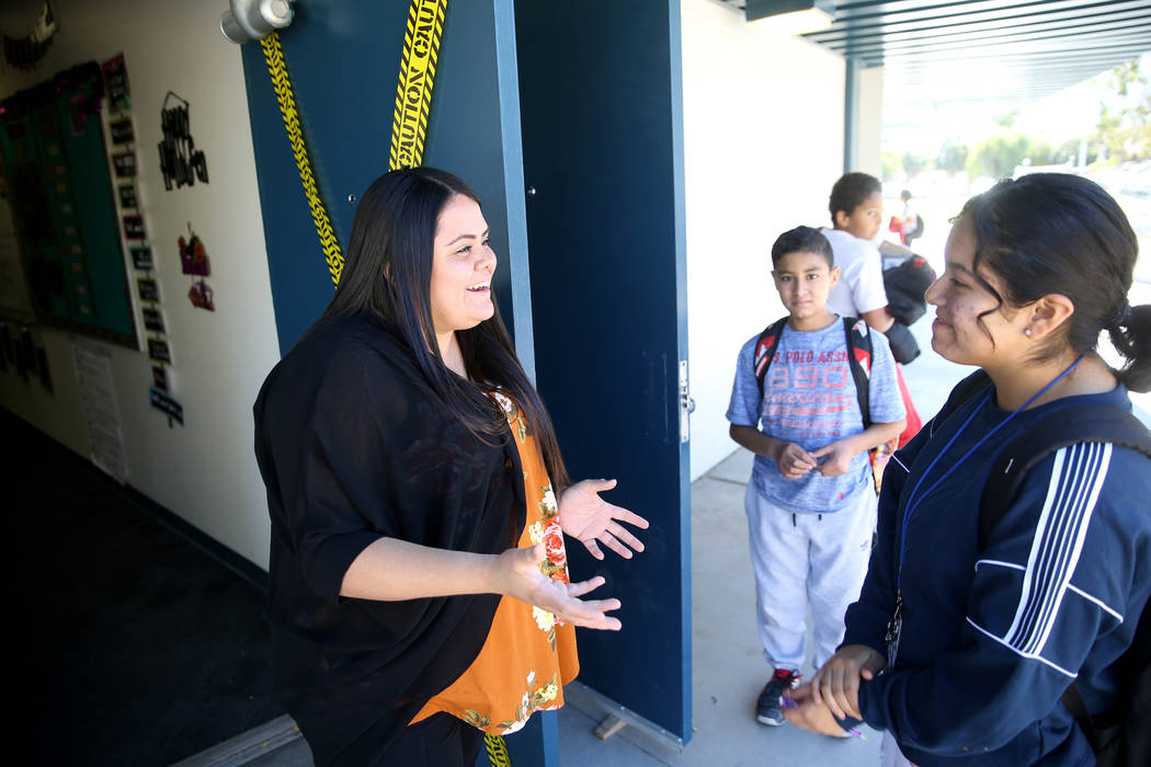 Teacher Myra Gomez congratulates seventh grader Diana Tobon on making the cheerleading squad du ...