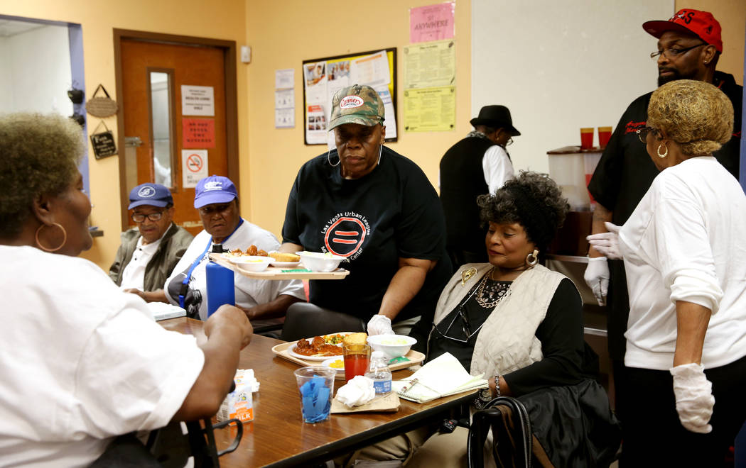 Willie Jones serves lunch to Magnolia Harper, 65, and Ada Glover, 76, at Martin Luther King Jr. ...