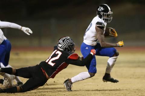 Desert Pines Javontae Barnes (22) breaks a tackle from Las Vegas Kevin Covarrubias (12) during ...