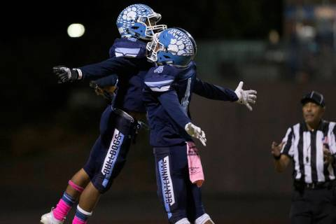 Centennial junior Gerick Robinson (6) celebrates with teammate Aaron Johnson (4) after Robinson ...