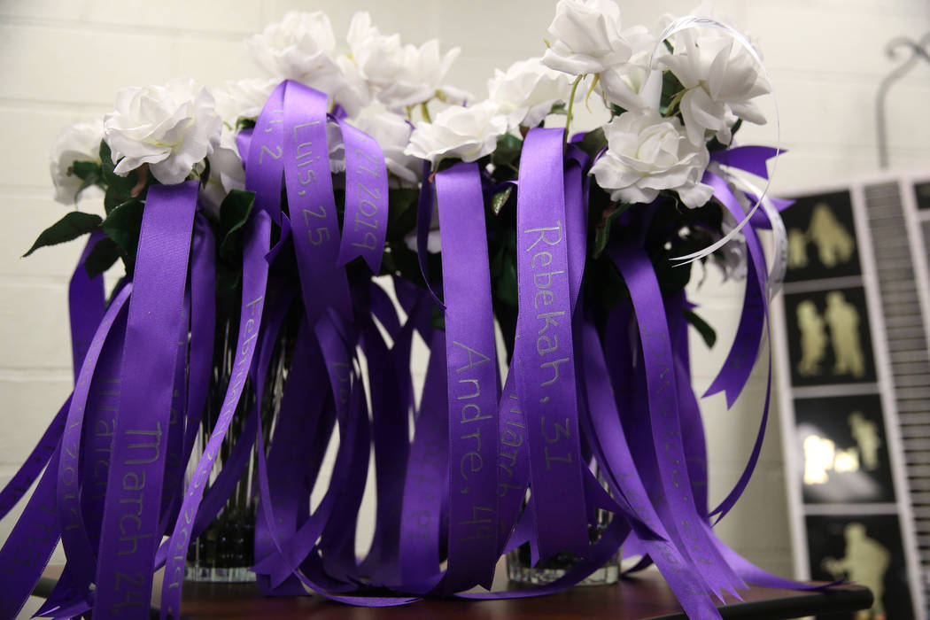 Flowers with the names of domestic violence victims are displayed during a domestic violence me ...