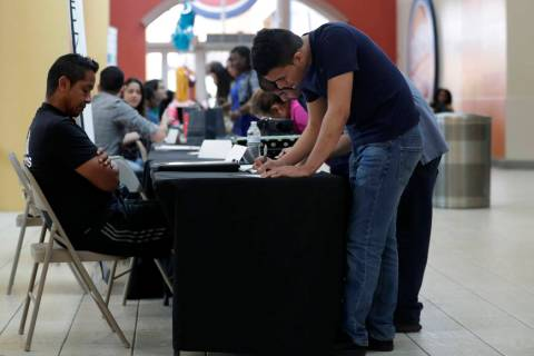 In a Oct. 1, 2019, file photo Billy Ramos, right, fills out a job application with Adidas durin ...