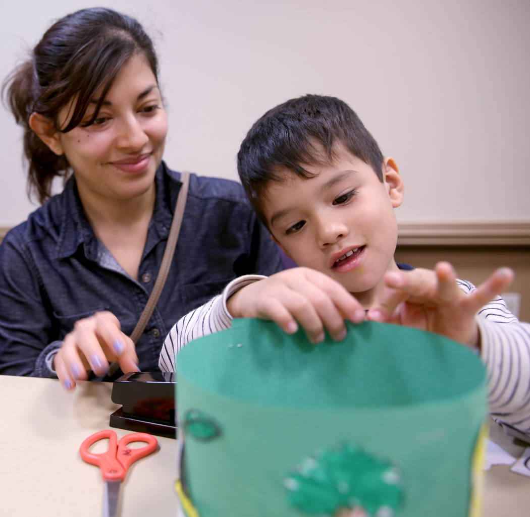 """Christian Falcon, 3, works on his """"life cycle hat"""" with his mom Berenice Falcon duri ..."""