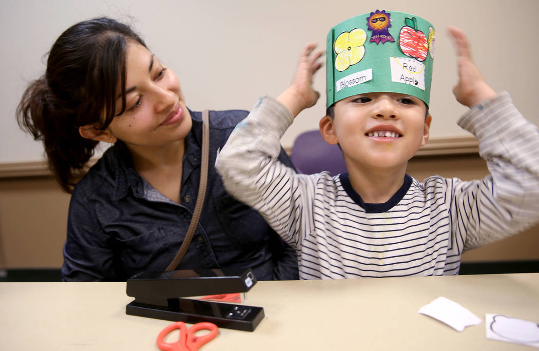 """Christian Falcon, 3, dons his """"life cycle hat"""" with his mom Berenice Falcon during a ..."""