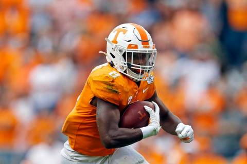 Tennessee running back Ty Chandler (8) runs for yardage in the first half of an NCAA college fo ...