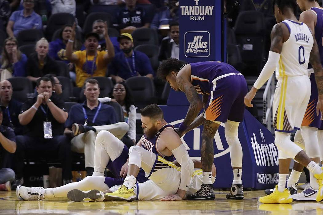 Phoenix Suns' Aron Baynes, left, gets up after falling onto Golden State Warriors' Stephen Curr ...