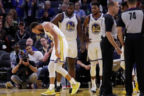 Golden State Warriors' Stephen Curry, left, grimaces after Phoenix Suns' Aron Baynes fell onto ...