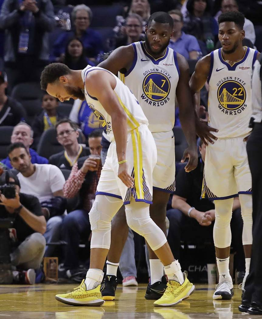 Golden State Warriors' Stephen Curry, left, grimaces as Eric Paschall (7) and Glenn Robinson II ...