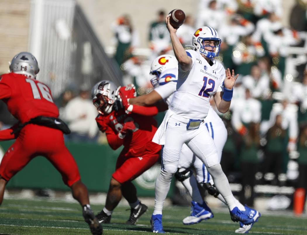 Colorado State quarterback Patrick O'Brien, front right, escapes the pocket to throw a pass as ...