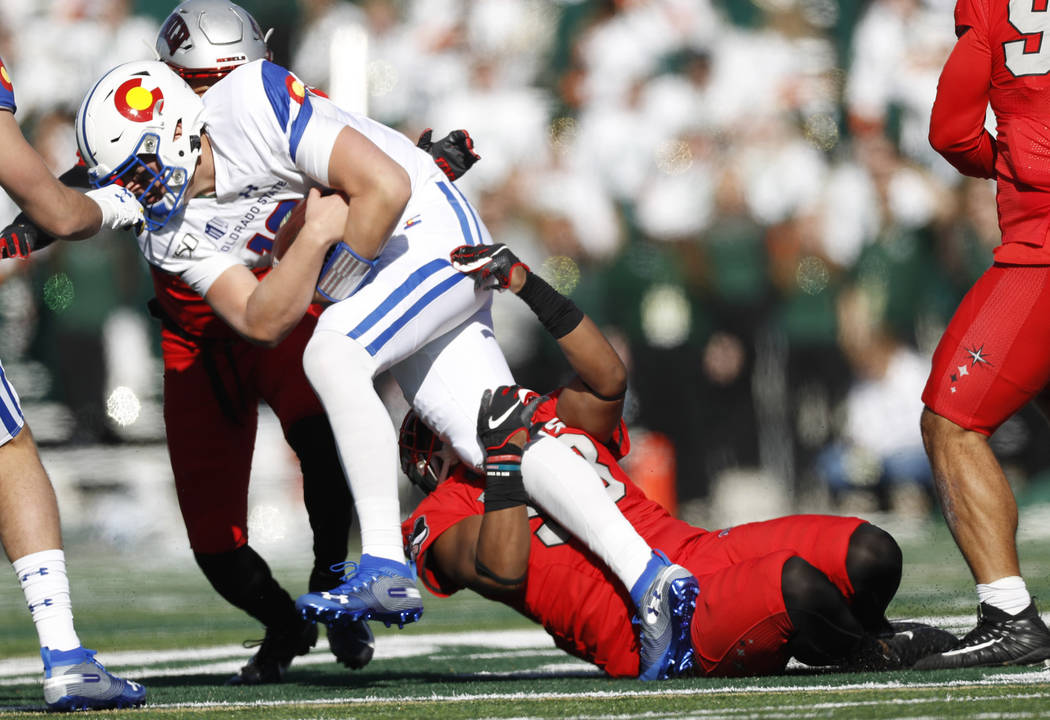 Colorado State quarterback Patrick O'Brien, left, is dragged down after a short gain by UNLV de ...