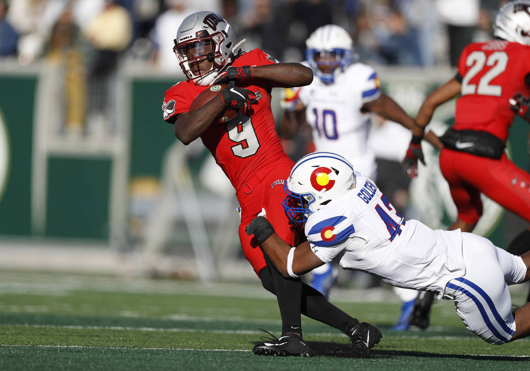UNLV wide receiver Tyleek Collins, left, is dragged down by Colorado State linebacker Troy Gold ...