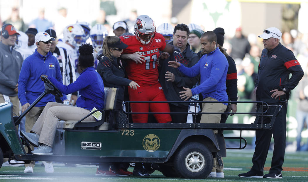 UNLV tight end Noah Bean, center, is helped onto a cart after being injured against Colorado St ...