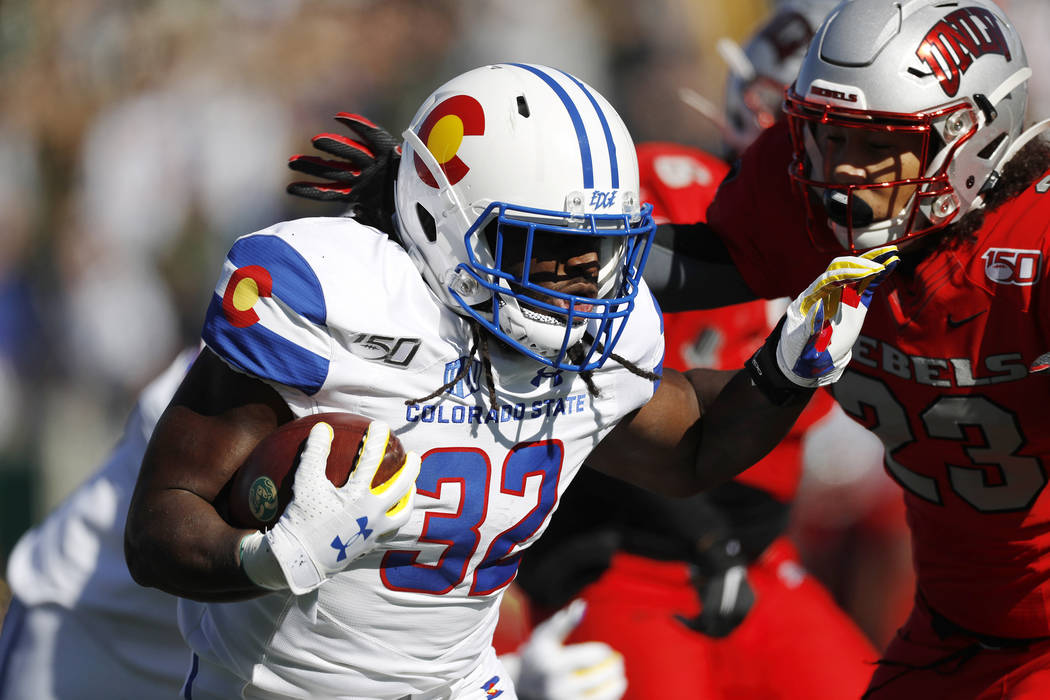 Colorado State running back Marcus McElroy, left, bulls past UNLV defensive back Greg Francis t ...