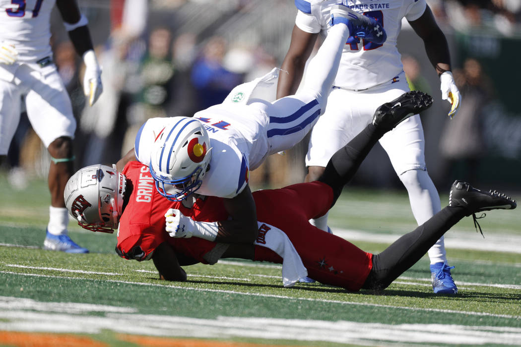 UNLV wide receiver Randal Grimes, bottom, is tackled after catching a pass for a first down by ...