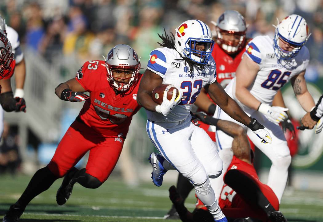 Colorado State running back Marcus McElroy, front, runs for a long gain with UNLV linebacker Fa ...