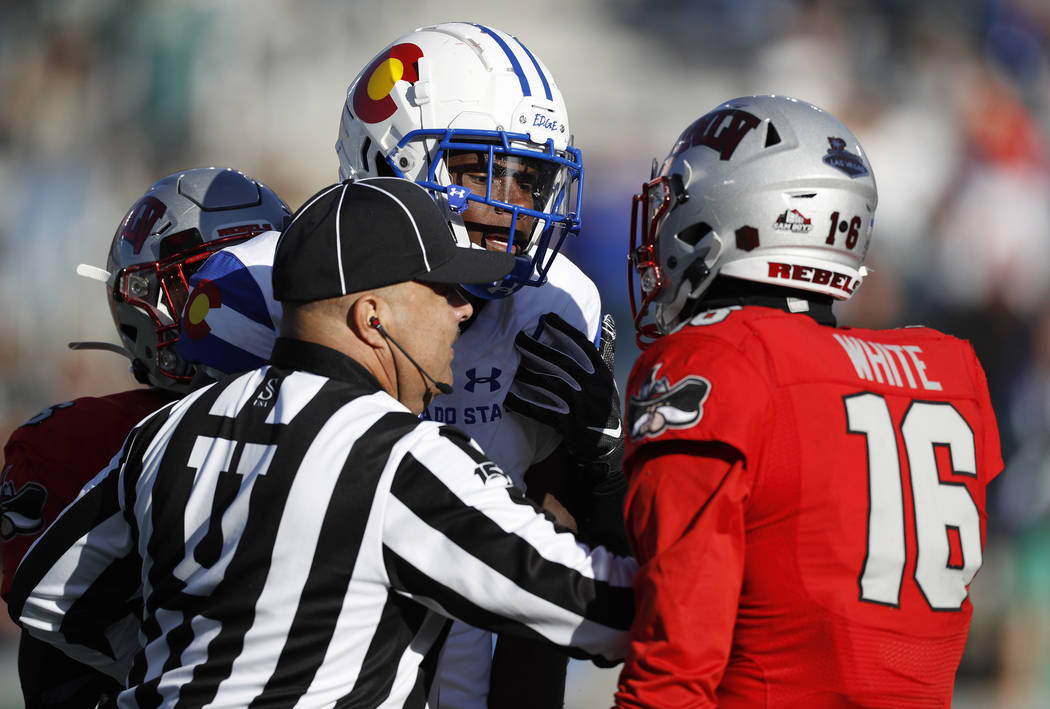 Umpire Rico Orsot, left, breaks up a skirmish between Colorado State wide receiver Warren Jacks ...