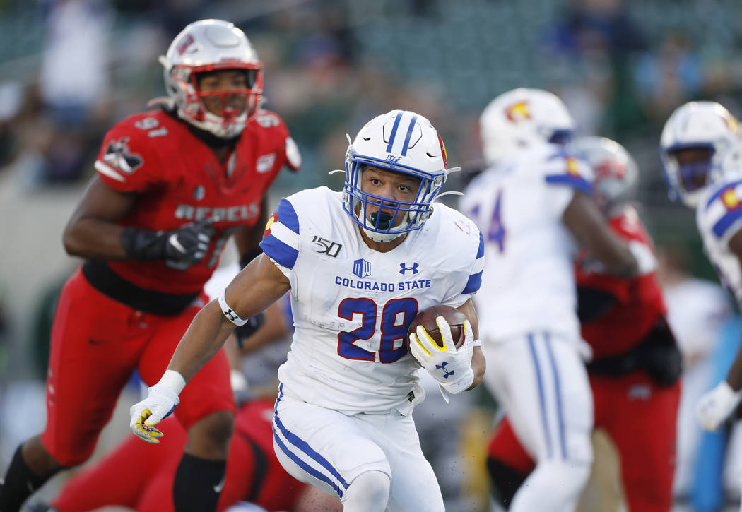 Colorado State running back Christian Hunter, front, runs for a long gain with UNLV defensive l ...
