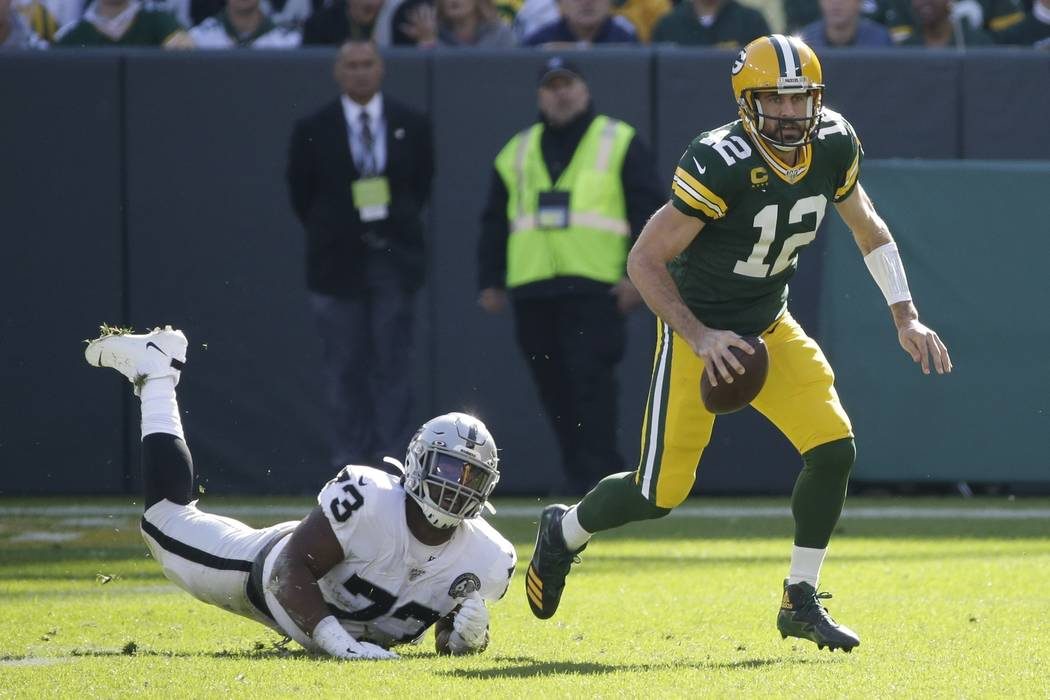 Green Bay Packers' Aaron Rodgers gets away from Oakland Raiders' Maurice Hurst during the first ...