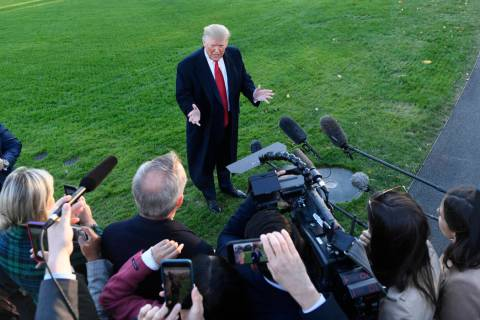 President Donald Trump talks to reporters on the South Lawn of the White House in Washington, F ...