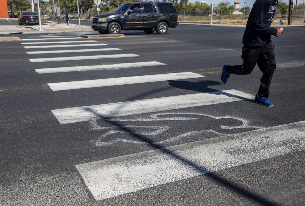 A pedestrian crosses chalk outlines freshly painted by the Las Vegas Fire Department at the int ...
