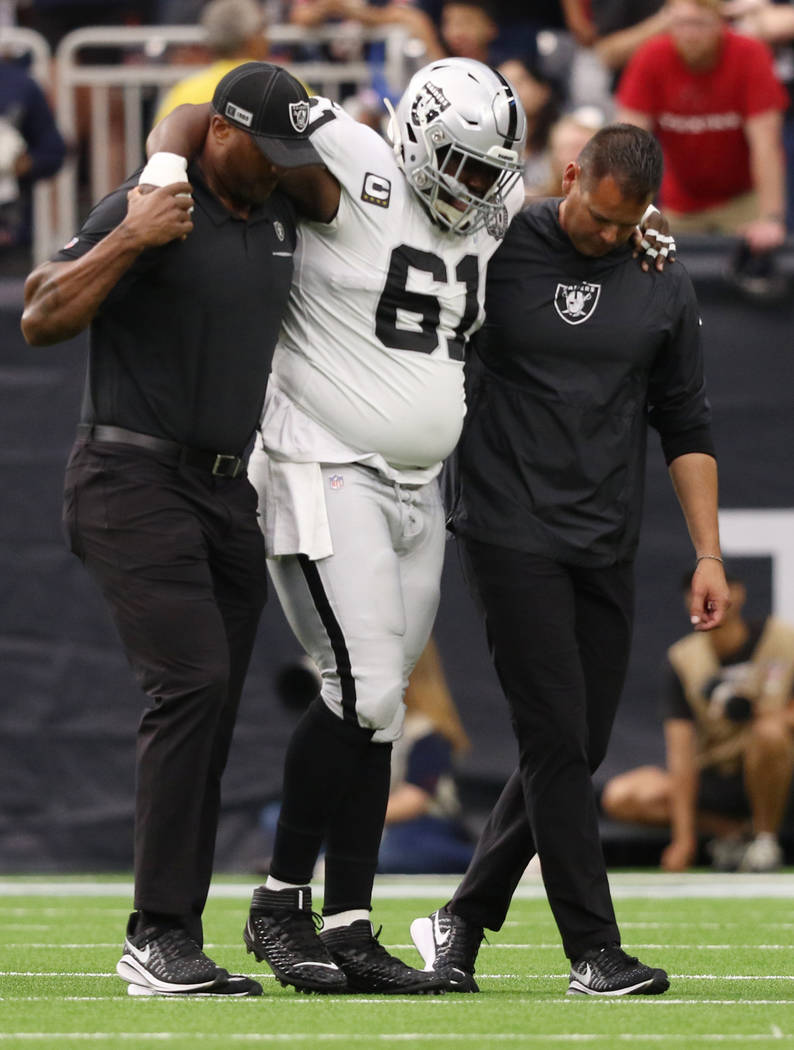 Oakland Raiders center Rodney Hudson (61) is helped off the field his trainers after sustaining ...