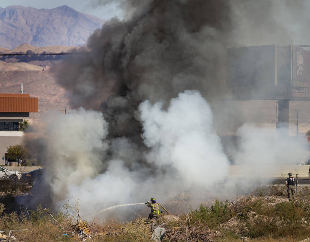 The Henderson Fire Department works a small brush fire just off of the southbound lanes of Inte ...