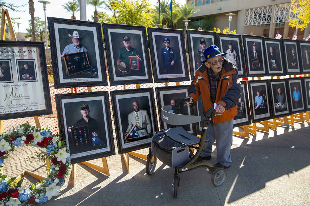 WWII Navy veteran Richard Swenson checks out his portrait by Mikel's Photography & Design w ...