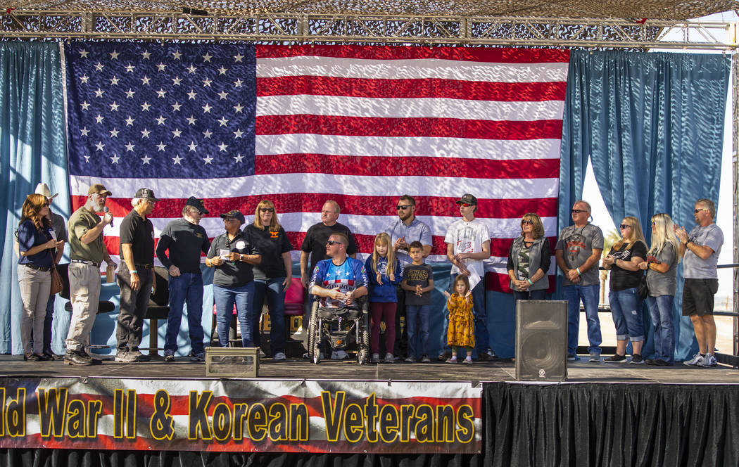 Veteran Tim Hall, center, surrounded by his family on stage receives a check during the 10th An ...