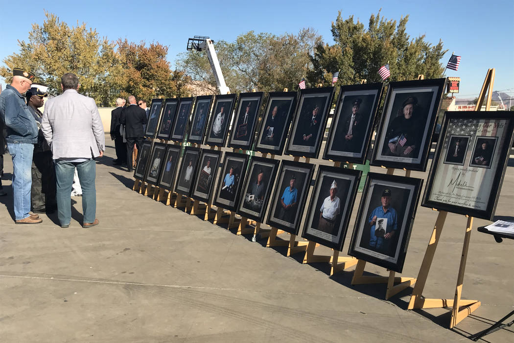 Attendees look at a photo display of veterans created by Mikel's Photography & Desig ...