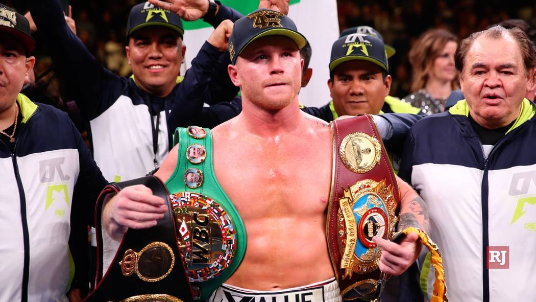 """Saul """"Canelo"""" Alvarez, right, holds his belts after winning at the MGM Grand Garden Arena i ..."""