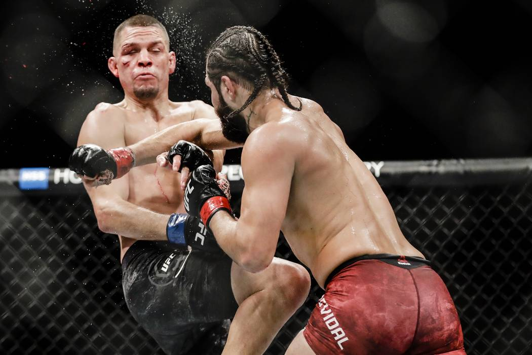 Jorge Masvidal, right, punches Nate Diaz during the third round of a welterweight mixed martial ...