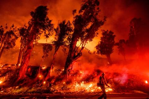 FILE - In this Nov. 1, 2019 file photo flames from a backfire consume a hillside as firefighter ...