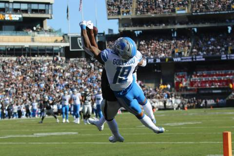 Oakland Raiders cornerback Daryl Worley, obscured, intercepts a pass intended for Detroit Lions ...