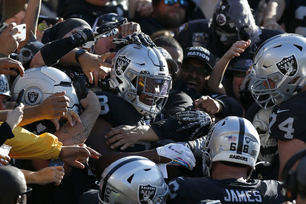 Oakland Raiders running back Josh Jacobs, center, celebrates with teammates and fans after scor ...