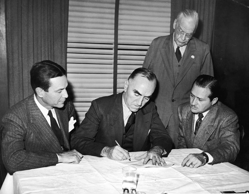 FILE - In this Nov. 14, 1945, file photo, Eddie Rickenbacker, center, signs papers selling the ...