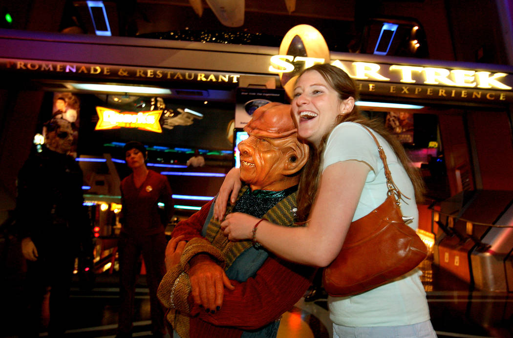 Tracy Jackson of Los Angeles, Calif., hugs an actor dressed as a Ferengi character at the entra ...