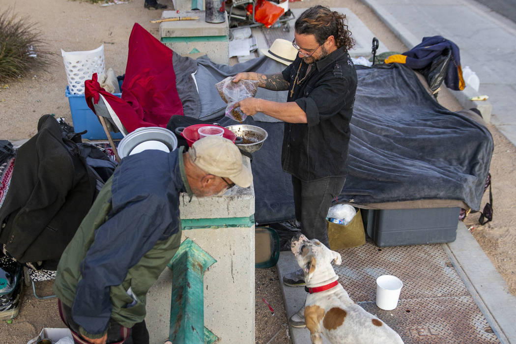 Kit Rogers, left, talks to Karma the dog as her owner James Miller pours her some dinner at a h ...