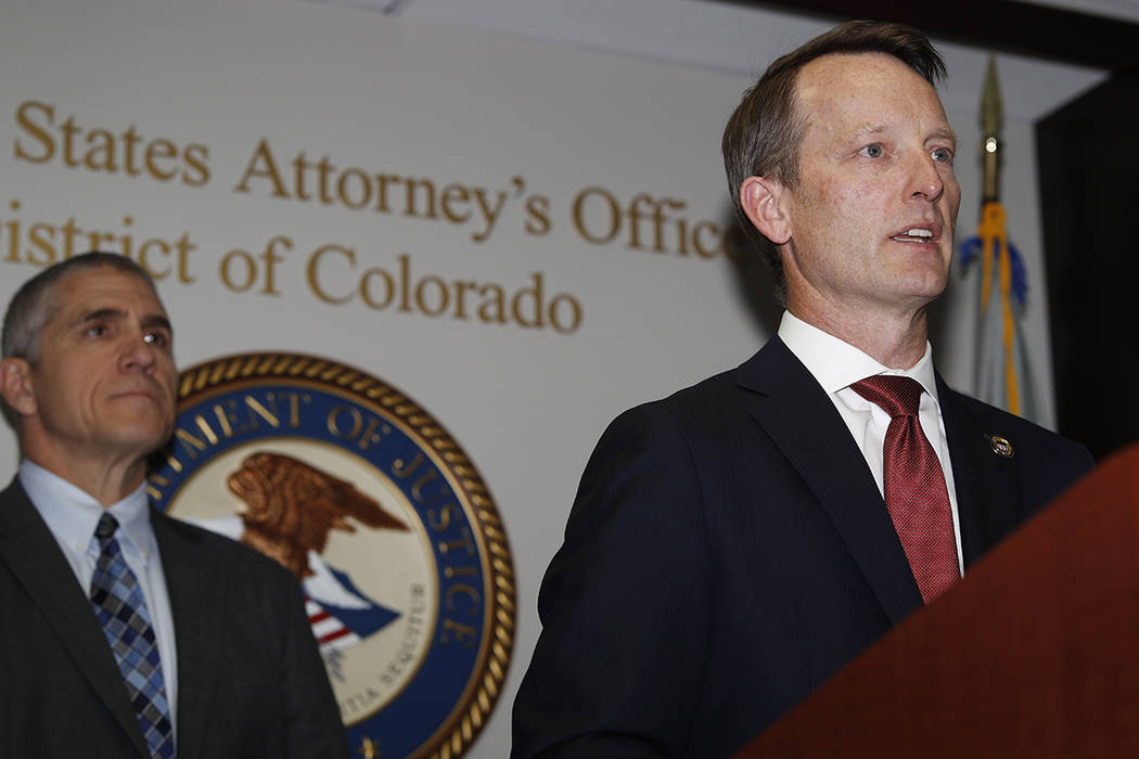 Jason R. Dunn, U.S. Attorney for the District of Colorado, right, makes a point as Dean Phillip ...