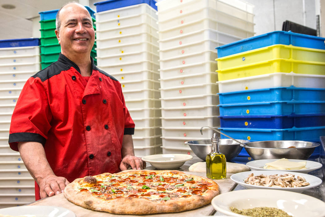 Chef/co-owner John Arena adds fresh basil to an Olde New York specialty pizza, with dozens of t ...