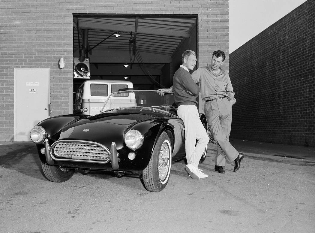 Actor Steve McQueen, left, and racer Carroll Shelby stand by McQueen's Ford-Cobra roadster, Jun ...