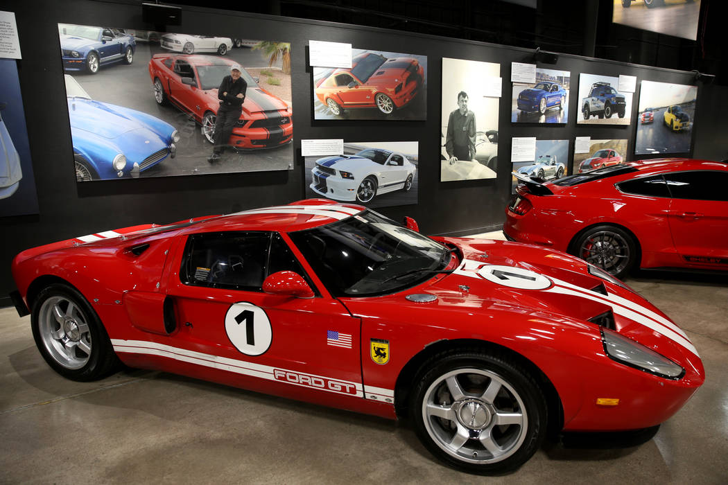 Photos of late car racing and car making legend Carroll Shelby above a 2004 Ford GT prototype, ...