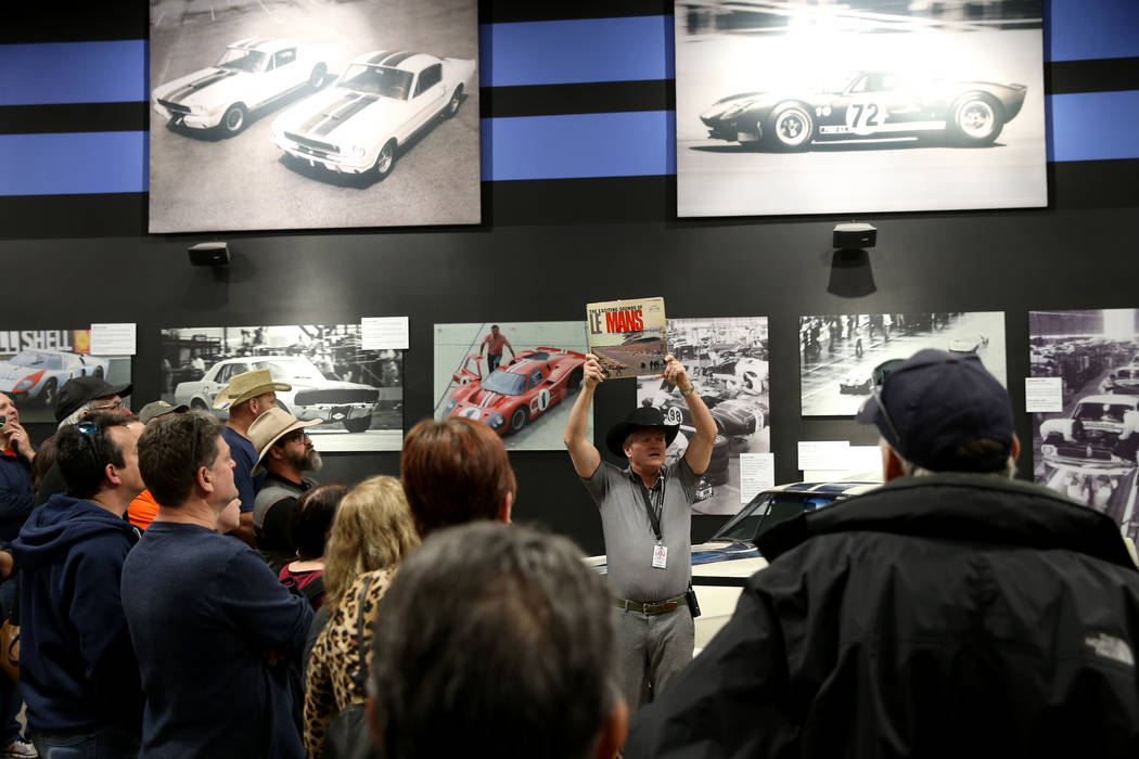Tour guide Mike Dempsey shows an album cover featuring a photo of the 1966 La Mans race that wa ...
