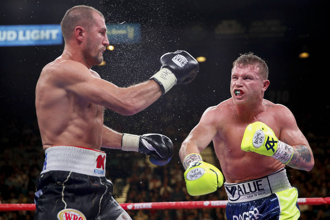 Sergey Kovalev, left, and Canelo Alvarez exchange punches during a light heavyweight WBO title ...