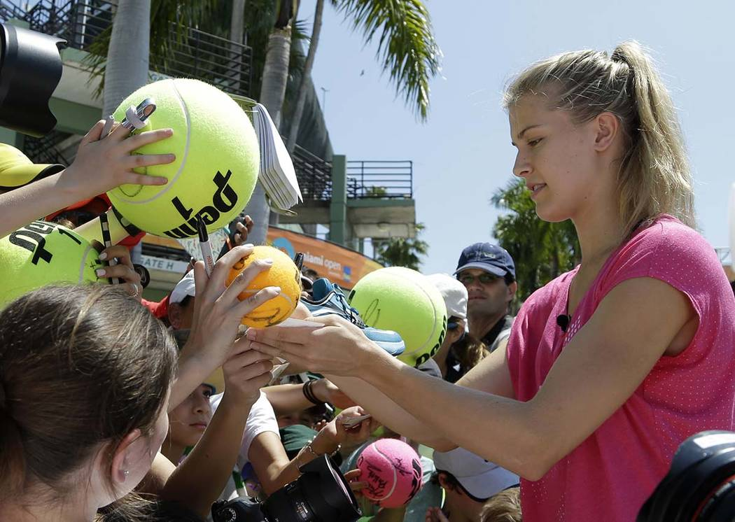In this March 24, 2015, file photo, Genie Bouchard, of Canada, signs autographs at the Miami Op ...