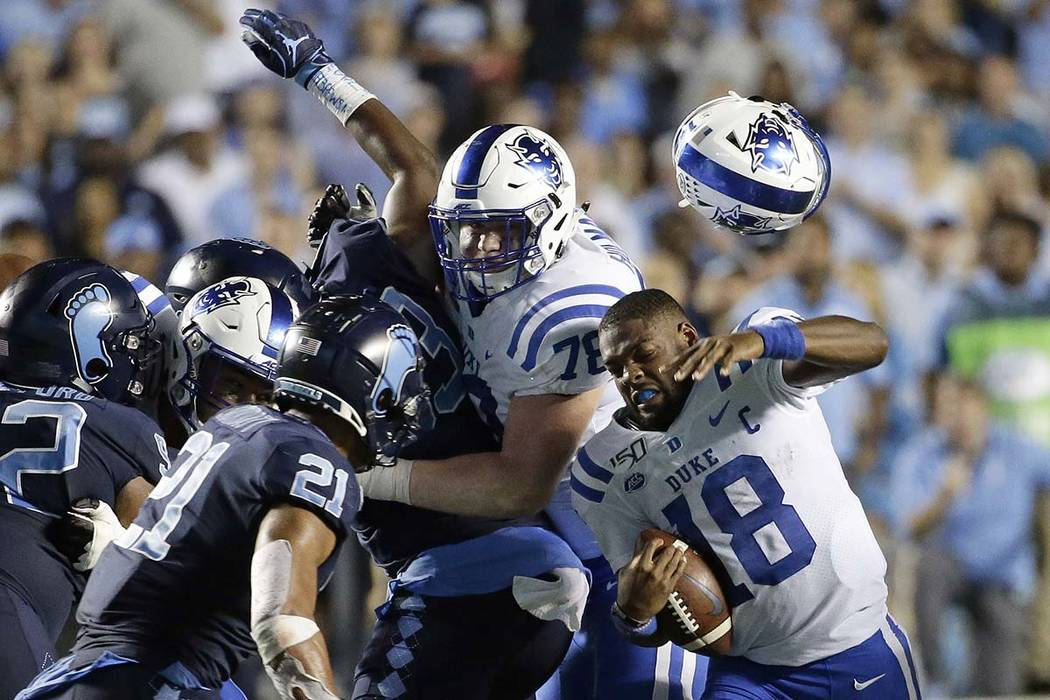 Duke quarterback Quentin Harris (18) loses his helmet during the second half of an NCAA college ...