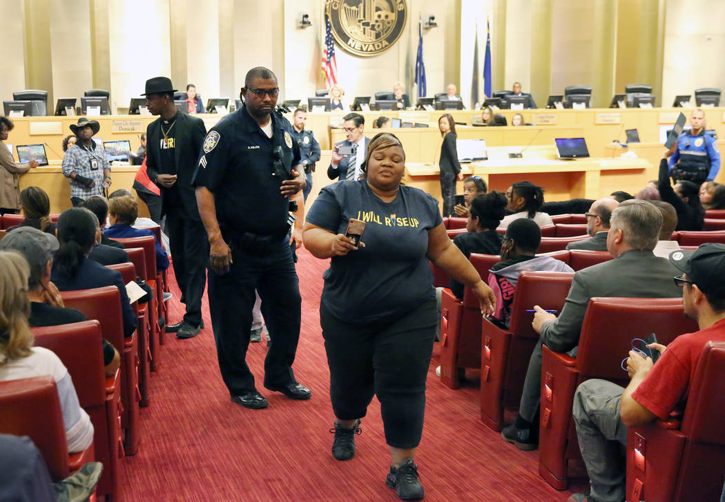 A protester was escorted out of the council meeting where people were protesting against the ci ...
