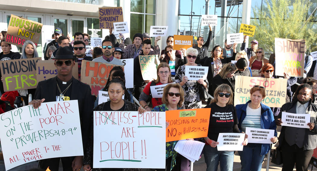 Protesters hold signs outside Las Vegas City Hall during a protest against the city council's c ...